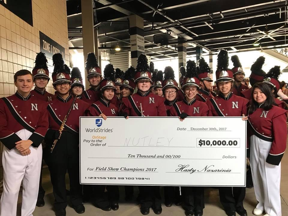 The band poses with the check before performing pregame, photo: Nutley Music Boosters Association