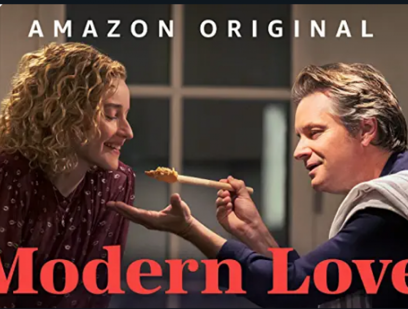 A man feeds a woman spaghetti on a wooden spoon. The words Amazon Original can be seen at the top, while the words Modern Love are seen at the bottom.