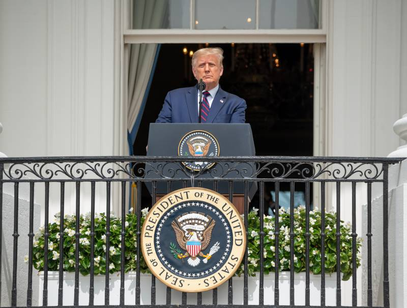 Donald Trump standing at a podium in front of the White House
