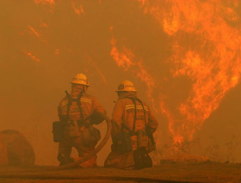 Firefighters combat the flames